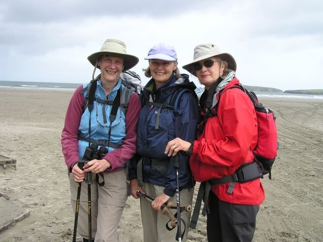 Three hikers on the beach