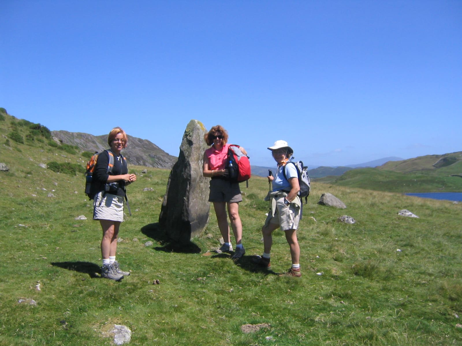 Image of walkers and standing stone in Wales, July