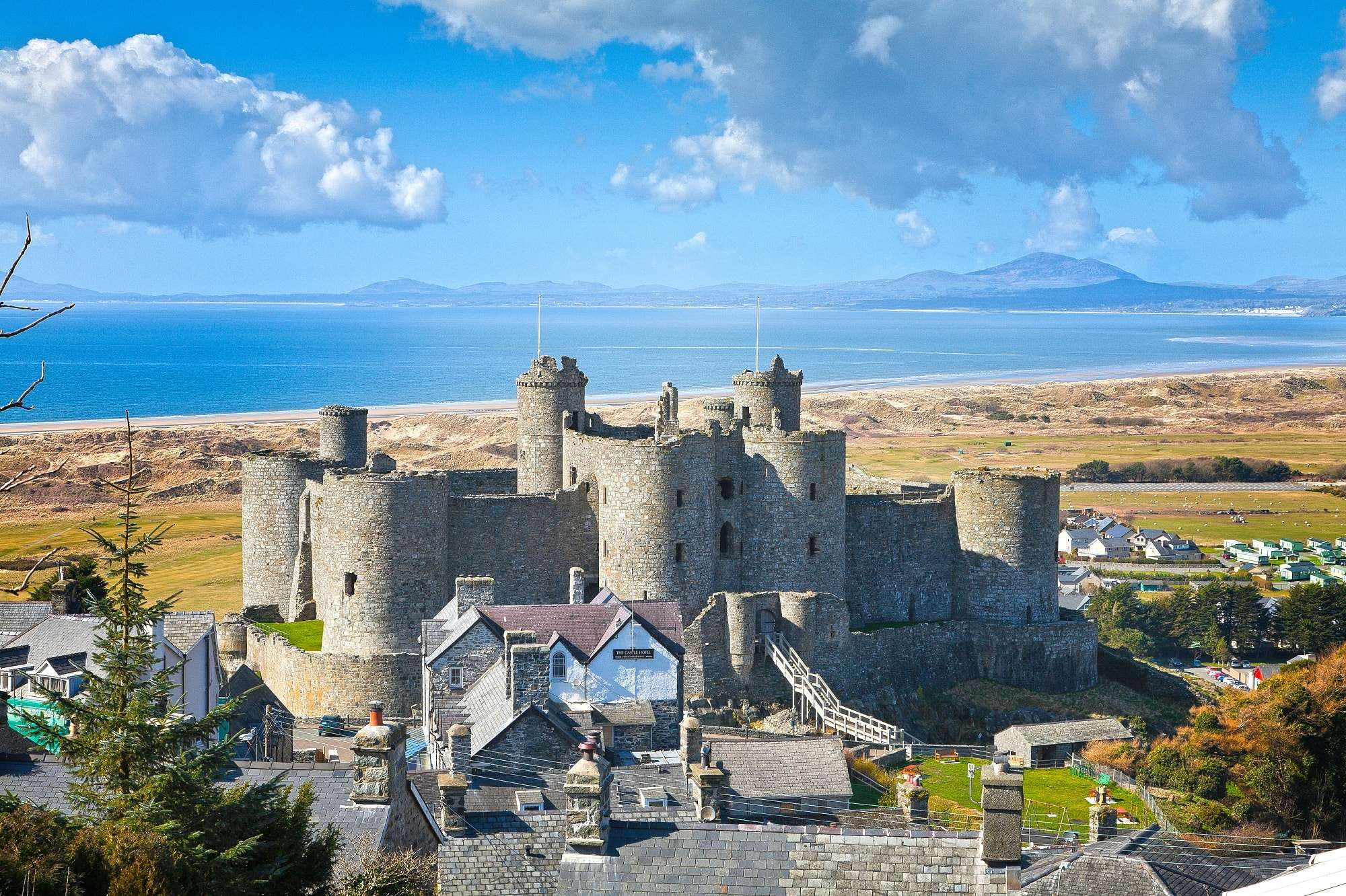 Ariel vew of Harlech castle, town and beach backdrop of the mountains in Snowdonia