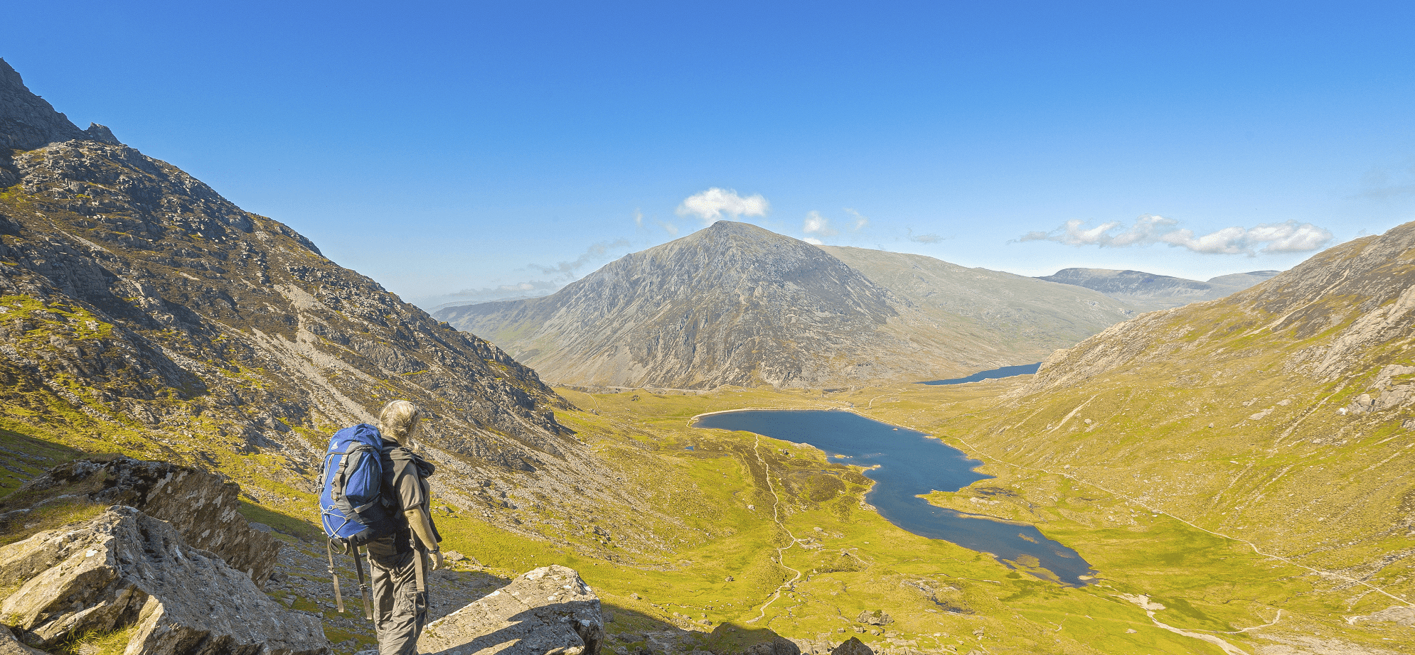 Walker on path down from devils Kitchen to Cwm Idwal with Llyn Idwal and Pen yr Ole Wen in shot