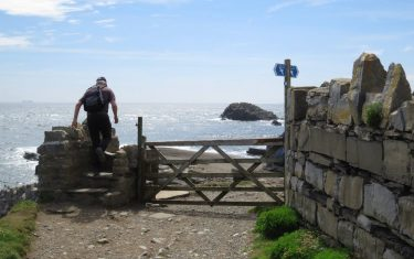 Climbing over a stile on the Isle of Man Coastal Path