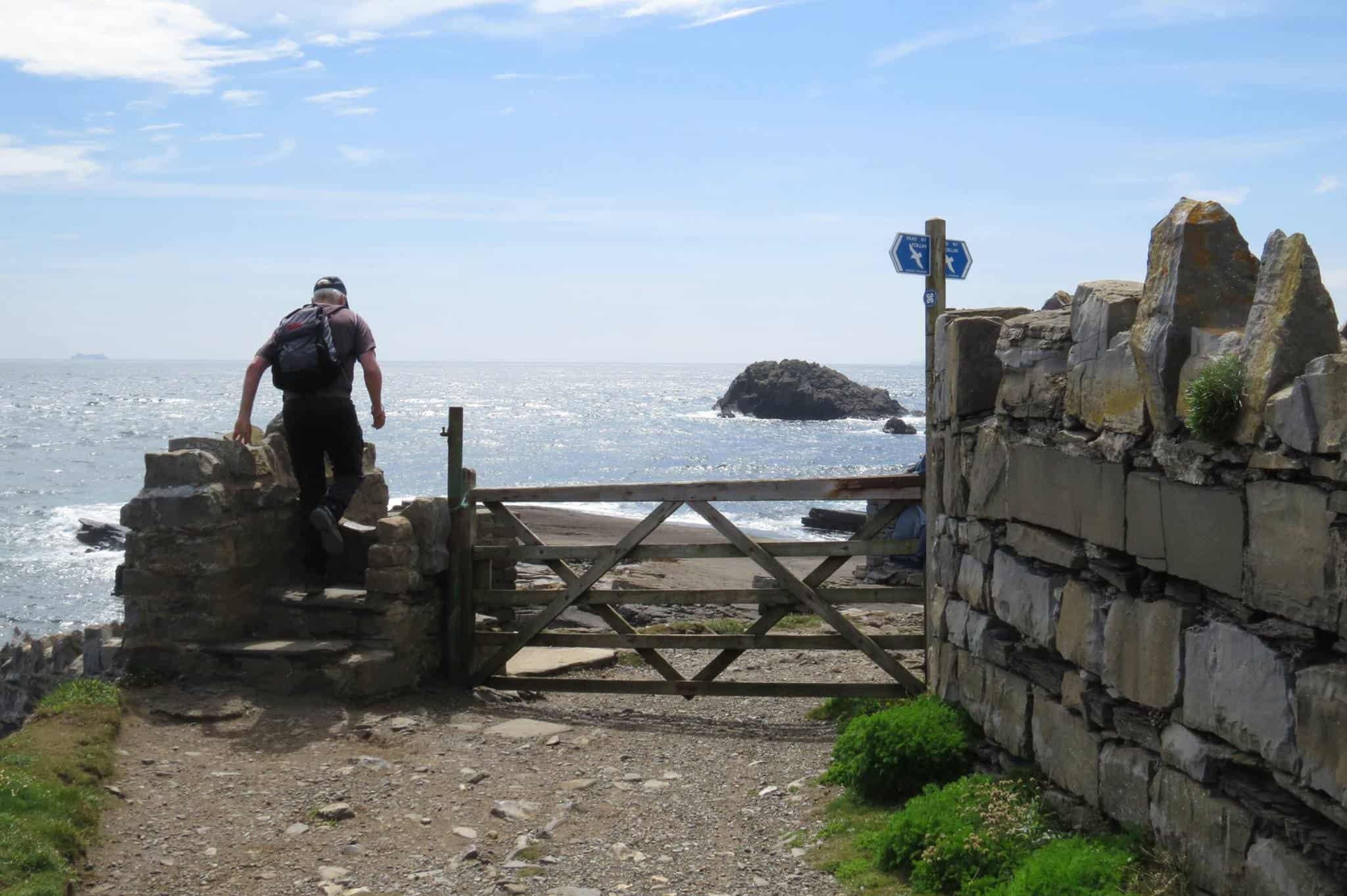 Climbing over a stile on the Isle of Man Coastal Path