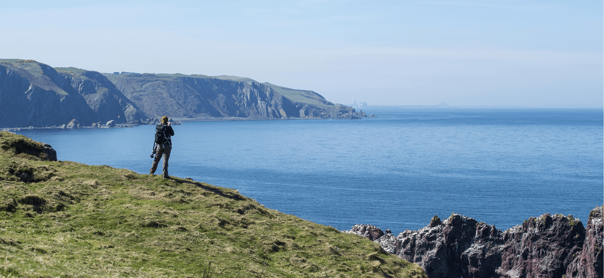 Man on cliff with binoculars